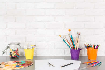 brush painting: Shot of a desk full of brushes, crayons and plasticine