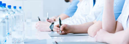 medical notes: Cropped picture of a group of doctors making notes during a conference Stock Photo