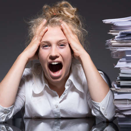 overwork: Young female accountant having a lot of paperwork Stock Photo