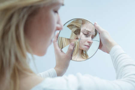 multiple personality: Close-up of a desolated young woman looking into a broken mirror which she is holding in her hands
