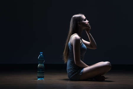 floor covering: Anorexic girl sitting on floor next to bottle of water, covering mouth with one hand, dark background. Stock Photo