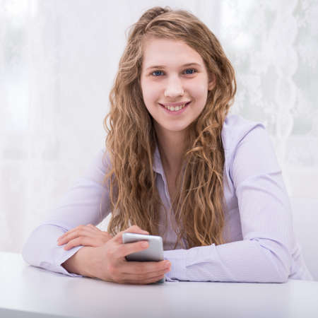 humiliated: Image of happy responsible teenager with new cellphone