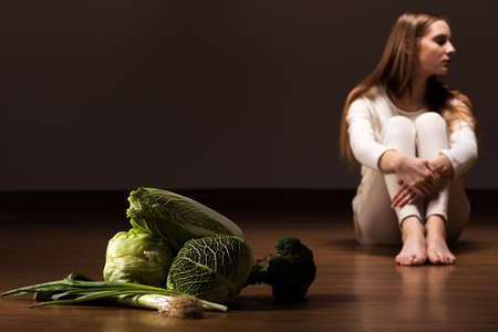rejecting: Girl rejecting food, sitting on floor, in the foreground green vegetables, dark background. Stock Photo