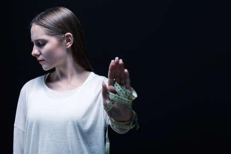 cinta metrica: La mujer joven, triste mantiene en la cinta de medida de la mano, de pie sobre fondo negro.