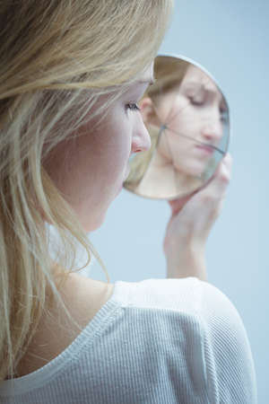 multiple personality: Close-up of a young woman looking into a broken mirror with grim face Stock Photo