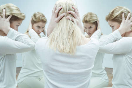 alter: Anxious young woman in white surrounded by her alter egos