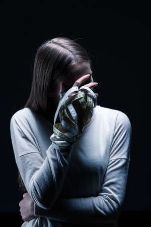 covering face: Bulimic woman covering face with one hand, holding measure tape, standing on black background.