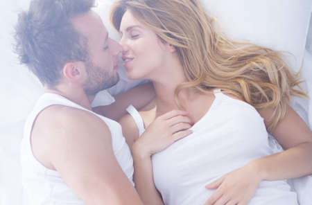 foreplay: Attractive couple is kissing tenderly in bed
