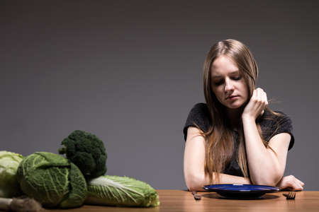 beside table: Girl sitting beside table, over an empty plate, in the foreground green vegetables, dark background.