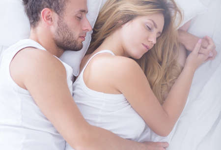 Beautiful young couple sleeping hugging in bed Stock Photo
