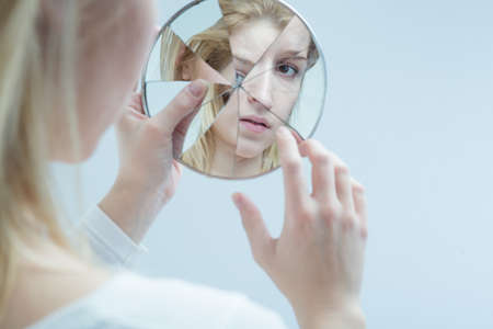 multiple personality: Young woman touching her own reflection in a broken mirror Stock Photo
