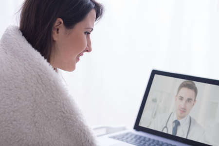 skype: Shot of a smiling young woman talking with a doctor