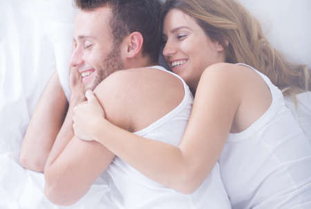 sexual foreplay: Young attractive couple is embracing in bed