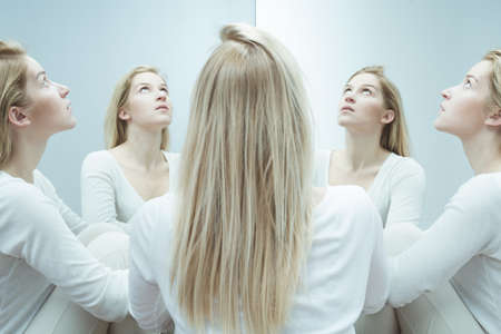 Young woman in white sitting among multiple reflections of her own, looking up