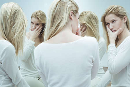 Young woman dressed in white, looking with worry at her alter egos