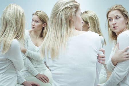 ansiedad: Foto de una mujer joven que mira con sorpresa y ansiedad a su propia semejanza imaginada