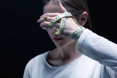 covering eyes: Girl covering eyes with one hand, holding measure tape, black background.