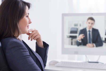 skype: Photo of two young colleagues having a video conversation at work
