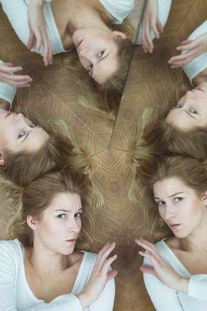 mirror on wall: Young woman lying on wooden floor by the mirror wall, looking anxiously at the camera, surrounded by her multiple reflections