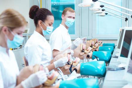 Drie jonge voorzichtig studenten leren op anatomische modellen hoe treat.Practice is het belangrijkste in het werk van tandarts Stockfoto