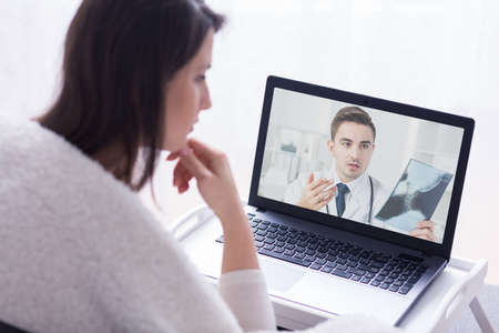 skype: Over the shoulder shot of a young woman and a doctor explaining her what he sees on an X-ray image
