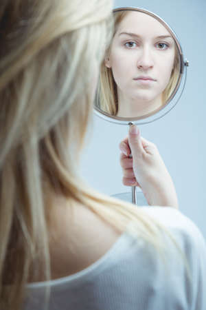 multiple personality: Close-up of a young, upset woman looking in the mirror she is holding in her hand Stock Photo