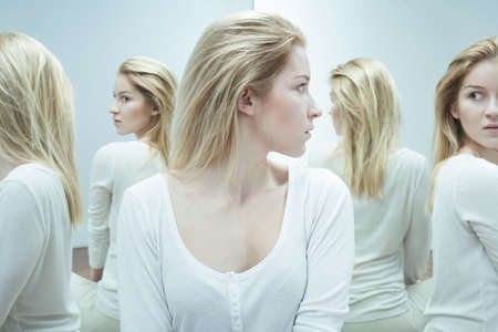 Shot of a young woman dressed in white, looking back with anxiety at her reflections in the mirror