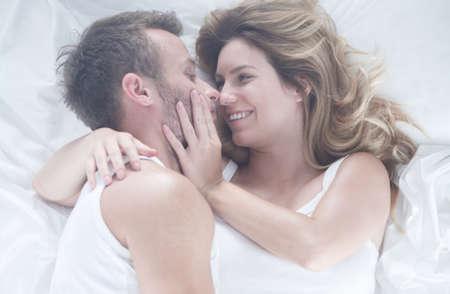 besos apasionados: joven pareja feliz se encuentra en la cama