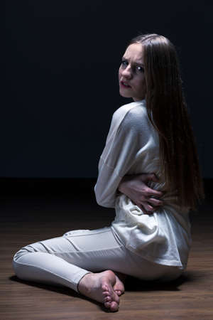 anorexia: Teenager with anorexia sitting on floor embracing herself, dark background. Stock Photo