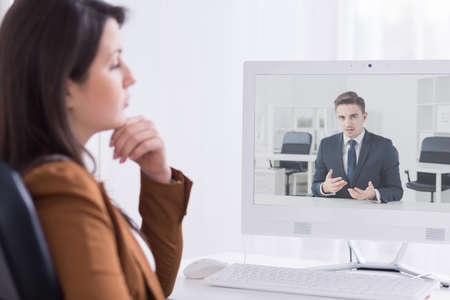 skype: Shot of young woman having a video conversation with her colleague