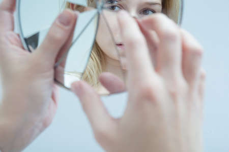 multiple personality: Close-up of a young woman touching a broken mirror which reflects her desolated face
