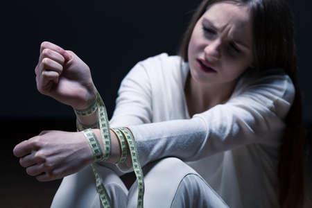 cinta metrica: Adolescente triste con cinta métrica alrededor de sus muñecas, sentado sobre un fondo oscuro.