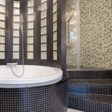 black bathroom: View of round bathtub inside black bathroom