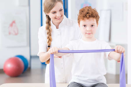 elastic band: Smiling young physiotherapist and her little patient exercising arms with elastic band