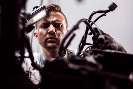 Mecánico de coche está pensando cómo reparar el coche