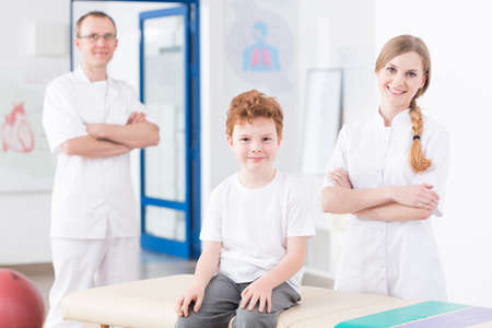 physiotherapists: Two experienced physiotherapists and little red head boy in pediatric rehabilitation clinic