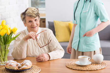 beside table: Happy senior woman sitting beside table and nurse standing next to hear in cozy interior Stock Photo