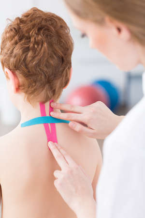 analgesics: Female physiotherapist applying colorful tapes on little boys cervical spine Stock Photo