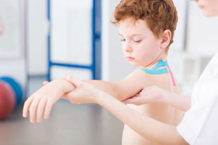 analgesics: Little cute red head boy having arm problem after injury. Physical therapist treating the patient with exercises Stock Photo
