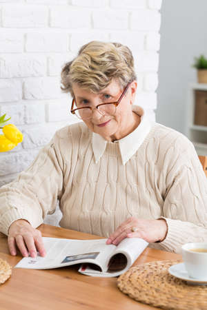 beside table: Senior woman in glasses reading a newspaper, sitting beside table in cozy interior