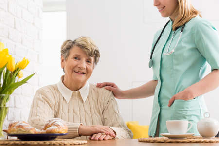 beside table: Senior woman sitting beside table and nurse with a stethoscope touching her arm