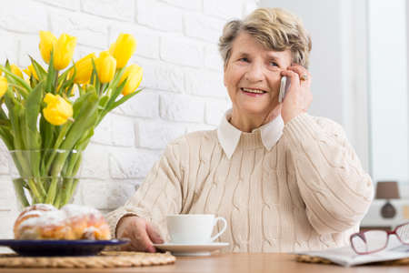 beside table: Senior woman sitting beside table, talking on a cellphone, smiling