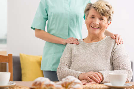 beside table: Happy senior woman sitting beside table and her carer