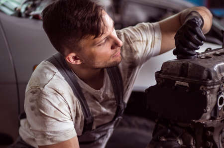 repaired: Young car mechanic is trying repaired fragment Stock Photo