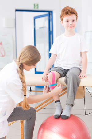 analgesics: Happy cute little kid on physical therapy in a clinic. Young pretty physiotherapist taking care of boy