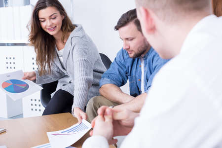 beside table: Woman and two young men sitting beside table at modern office Stock Photo