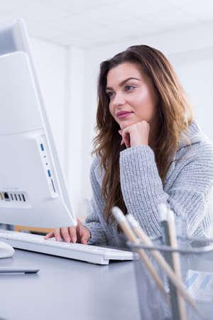 usando computadora: Joven mujer durante el trabajo, utilizando equipo, sentado junto a la mesa en el interior moderno