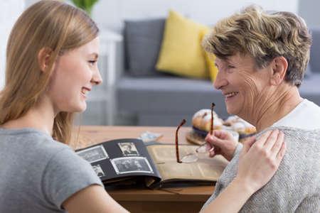 幸せな年配の女性と彼女の孫娘の写真アルバムを見て笑みを浮かべて