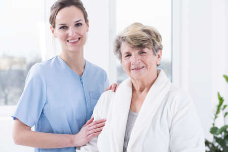 patient care: Happy senior woman and her professional carer, standing in light interior Stock Photo