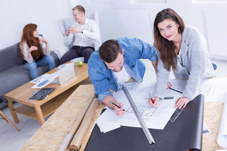 beside table: Man and woman standing beside table, drawing project, working at modern office